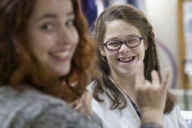 Alumna con necesidades especiales sonríe a la cámara mientras habla con su profesora en lengua de signos