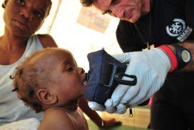 Bombero de BUSF prestando ayuda humanitaria a un niño durante el terremoto de Haití.