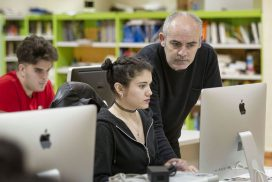 Alumna trabajando en un ordenador junto a su profesor